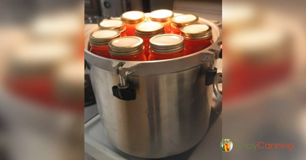Reusable canning lids on jars that are stacked in the pressure canner.