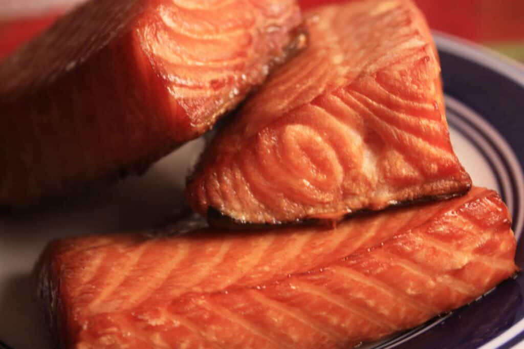 Flaky pieces of smoked salmon sitting on a plate.