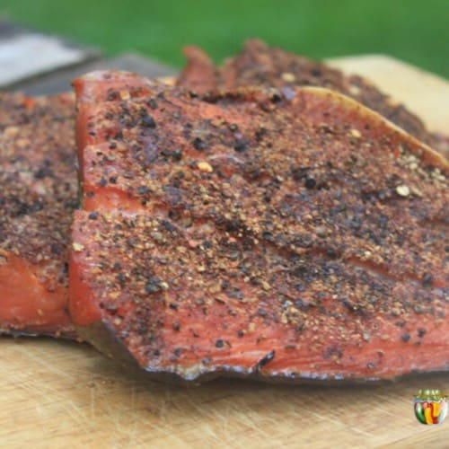Smoked salmon coated with pepper and sitting on a wooden board.