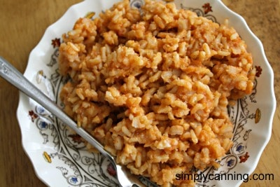 Spanish rice served on a fancy plate with a fork on the side.