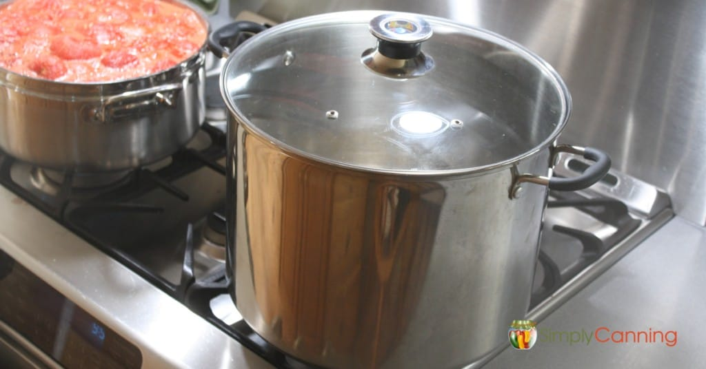 Stainless steel water bath canner sitting on the stove next to a pot of boiling jam.