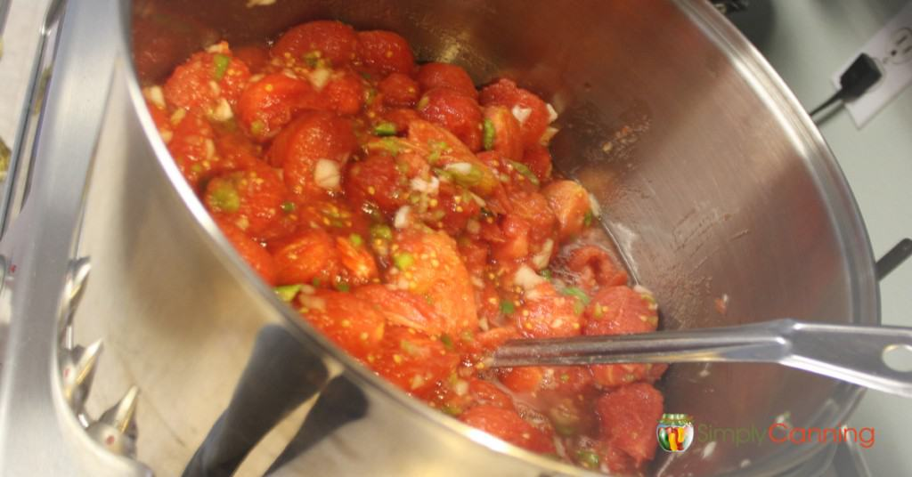 Stirring a stockpot filled with peeled tomatoes and chopped veggies.