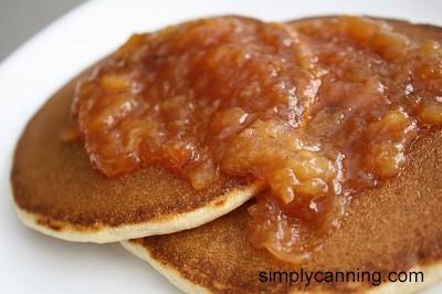 Stone fruit jam spread over pancakes.