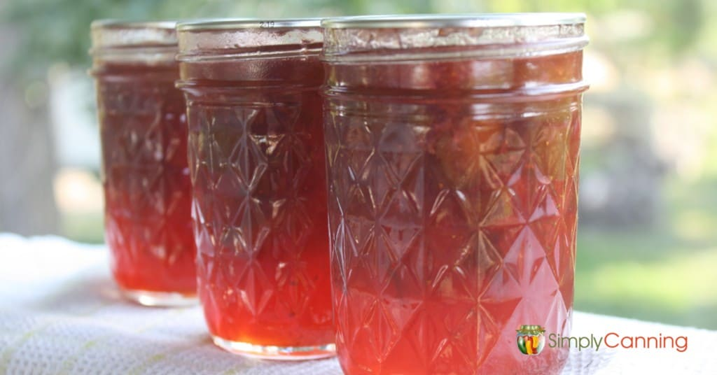 Three small jars of strawberry rhubarb jam that is a bright red color.