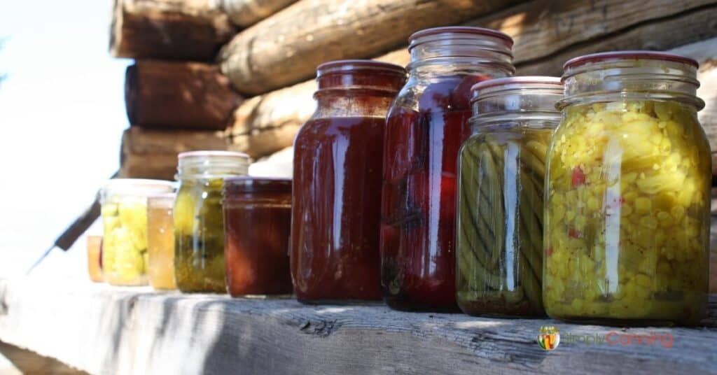 Jars of colorful home canned food lined up on a wooden ledge.