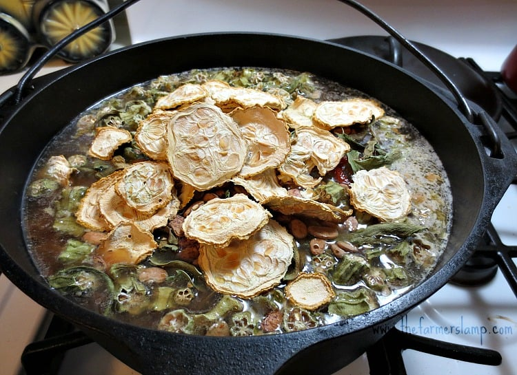 Putting dried vegetables into the pot of soup to cook.