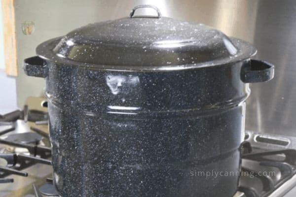 Black graniteware water bath canner sitting on the stovetop.