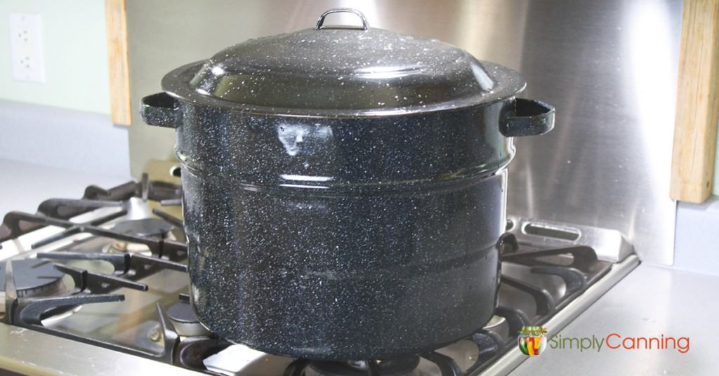 Black graniteware water bath canner sitting on the stove.